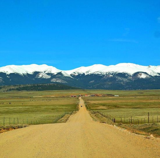 Clear Sky Blue The Way Forward Landscape Colorado Photography Rural Scene Colorado Snowcapped Mountain Mountain Tranquil Scene Diminishing Perspective Road Transportation Tranquility Vanishing Point Dirt Road Mountain Range Long Scenics Nature Beauty In Nature Field Empty Road