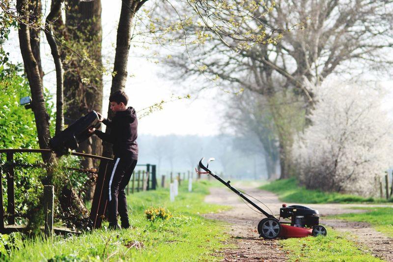 Boy with gardening equipment on pathway