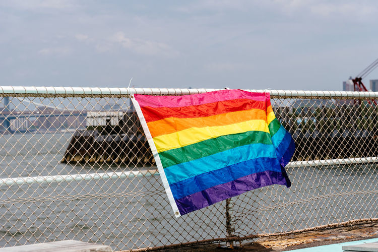 Rainbow Flag Hanging On Chainlink Fence Against Sky