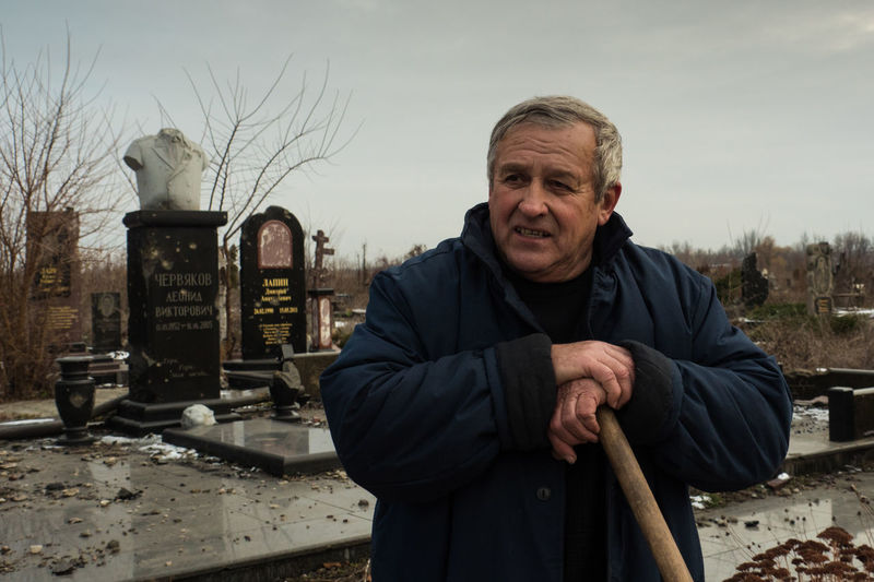 Local gravekeeper continues his work in cemetery that bears marks of heavy fire. To the question whether he is not afraid to walk on a grass full of unexploded ammunition he jokes that he steps lightly in his slippers. The war in Donbas has since its start in March 2014 caused more than 10 000 casualties and displaced over 1 million of people. Caretaker DPR Damage Photojournalism Russia Ukraine Conflict Dnr Documentary Donbass Doneck Military Rebel Senior Adult Separatist Territory War