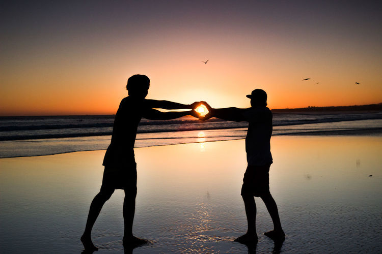 Silhouette of two men holding the sun on the beach at sunset