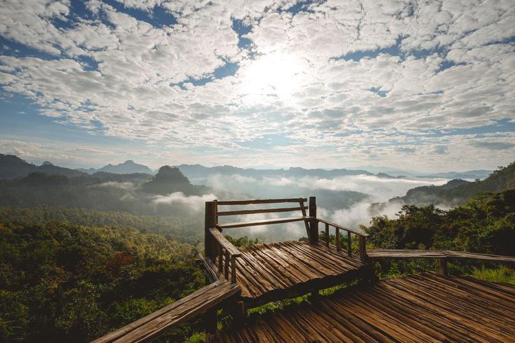 Bench on landscape against sky