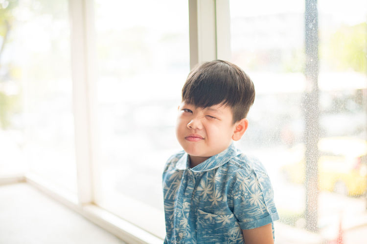 Portrait of cute boy sitting against window at home