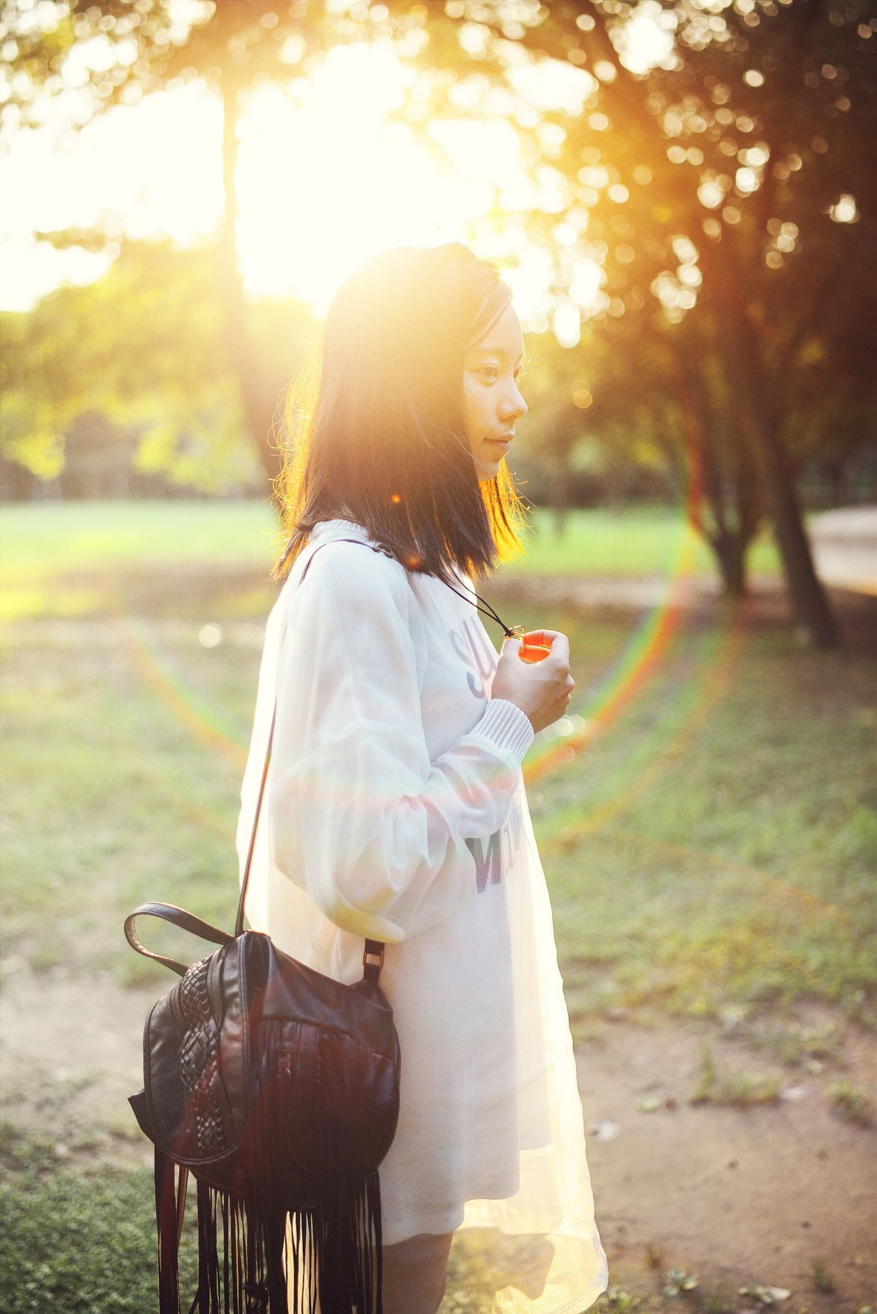 lifestyles, leisure activity, casual clothing, sunbeam, sunlight, focus on foreground, person, tree, sun, full length, lens flare, young adult, standing, side view, outdoors, rear view, holding, park - man made space