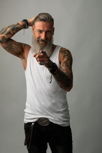 Portrait of a casual bearded hipster isolated on a white background is pointing with his finger of you One Person Front View Standing Males  Beard Casual Clothing Studio Shot Mature Adult Mature Men Portrait Cut Out Standing Modern Tattooed Bearded Pointing Finger Hair Hairstyle Fashion Jeans Shirt Biker Hioster Isolated