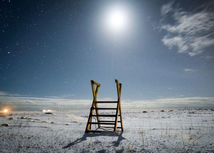 Wooden ladder on snow covered landscape against sky