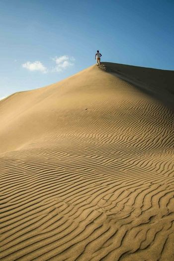 Man walking on sand dune in desert against sky
