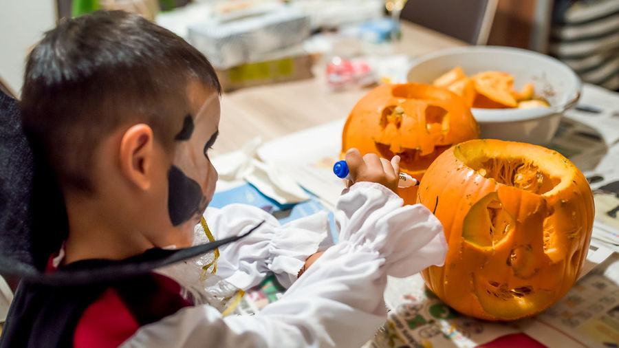 High angle view of boy and pumpkins