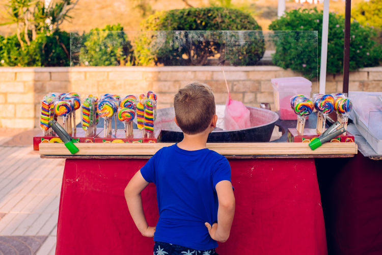 Rear view of boy standing at store