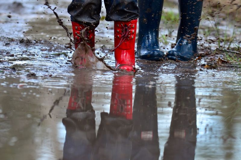 Low Section Of People Wearing Rubber Boots While Walking On Mud