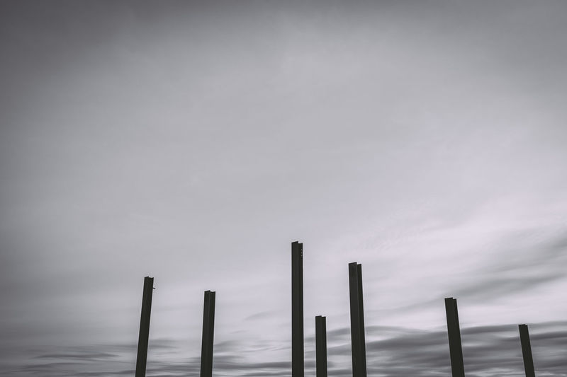 Low angle view of poles against sky