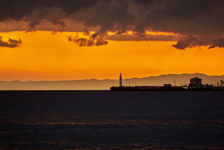 Silhouette pier by sea against orange sky