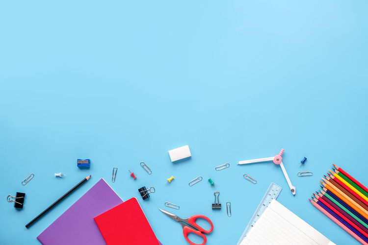 High Angle View Of School Supplies Over Blue Background