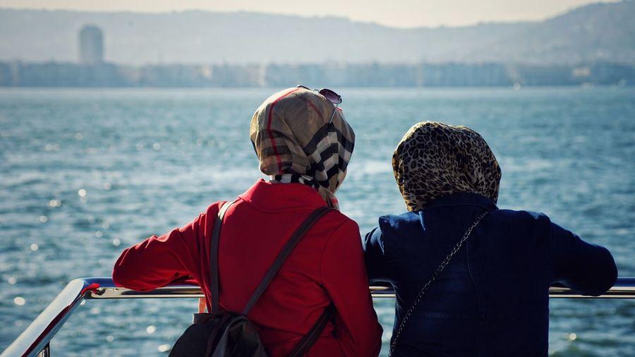 Rear view of women wearing headscarf looking at sea