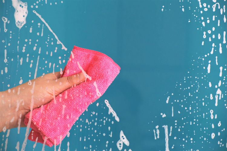Cropped hand cleaning wet glass window with rag against turquoise background