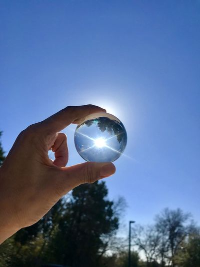 Cropped hand holding crystal ball against clear blue sky