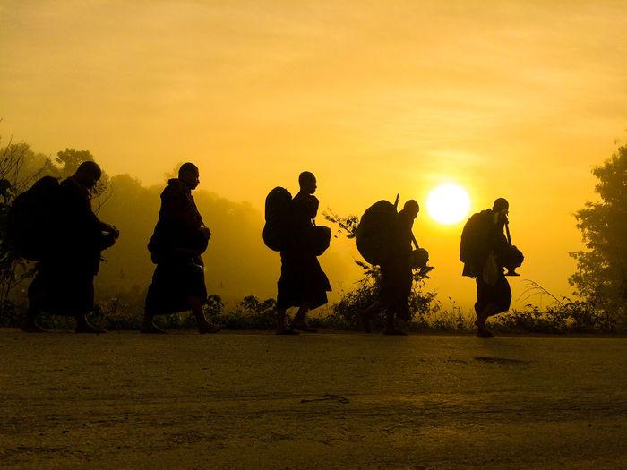 Silhouette men standing against sky during sunset