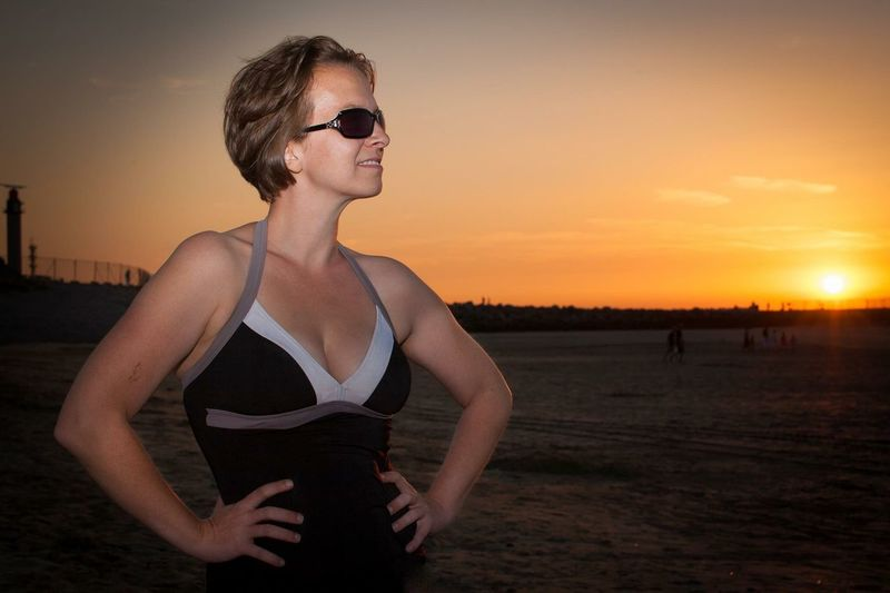 Woman Wearing Sunglasses Standing At Beach During Sunset