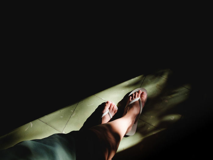Low Section Of Woman Legs Against Black Background