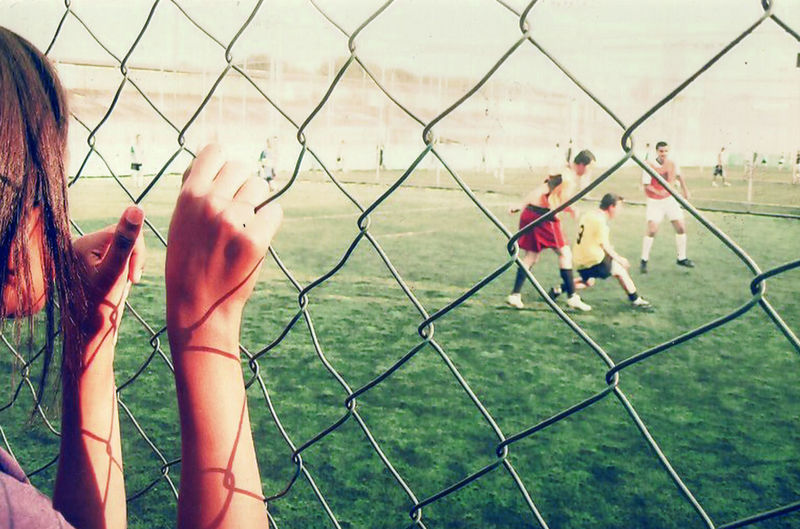 Children playing on field seen through chainlink fence