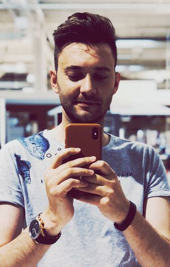 Young Men One Person Young Adult Lifestyles Real People Smart Phone Leisure Activity Focus On Foreground Selfie Technology Wireless Technology Mobile Phone Photography Themes Photographing Front View Holding Portable Information Device Photo Messaging Indoors  Portrait