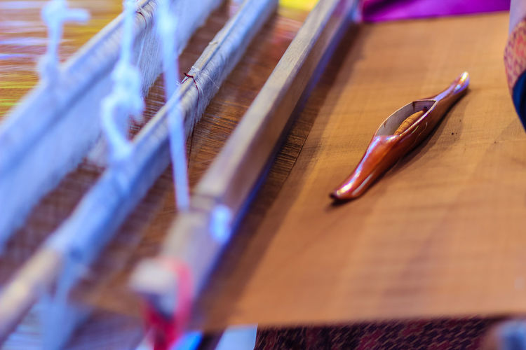 Weaver using small loom or weaving machine for weaving fabric. Weaver is weaving show and teaching to the tourist at the night market. Weave Weaves Close-up Day Indoors  Loom No People Selective Focus Weave Pattern Weaved Weaver Weaving Weaving Loom Weaving Machine Workshop