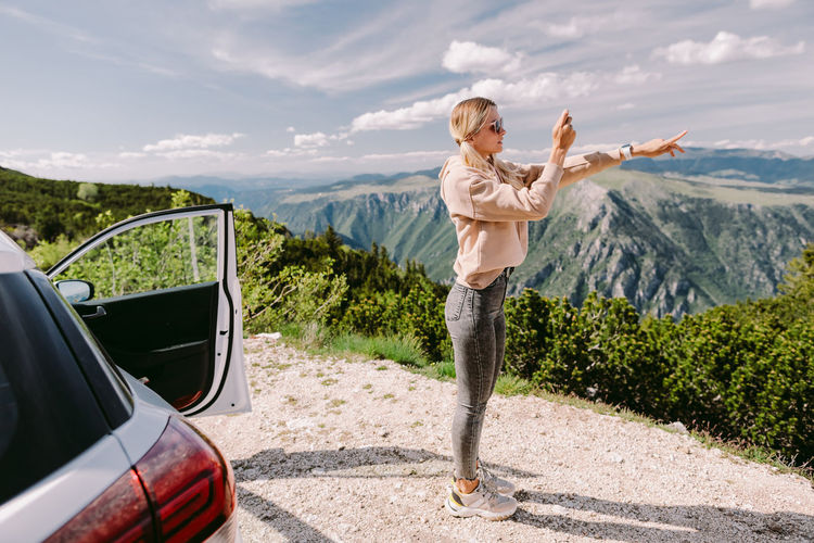 Woman standing by car on mountain road