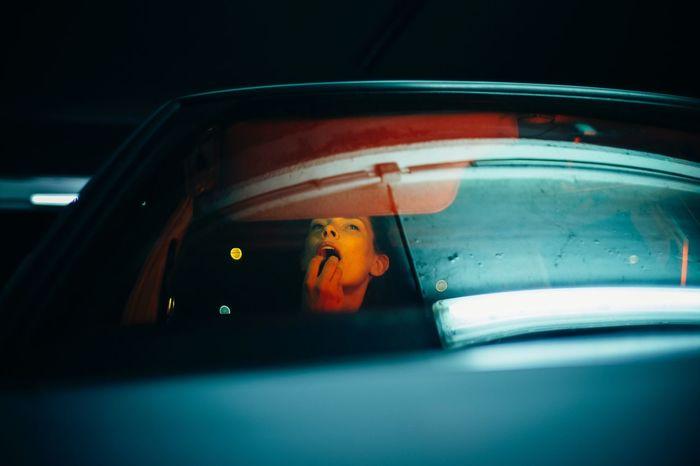 Woman seen through car window