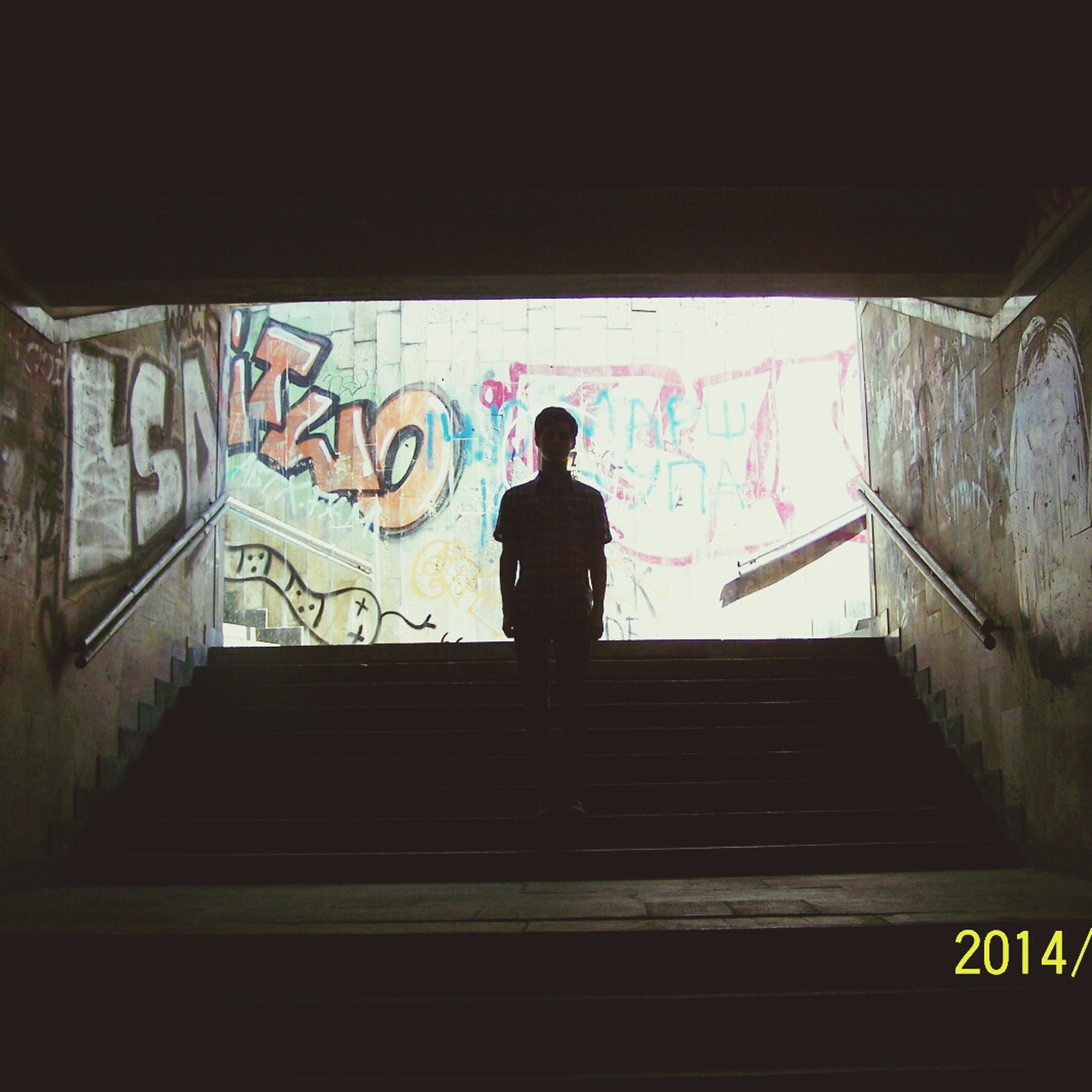 graffiti, text, architecture, built structure, lifestyles, full length, western script, indoors, communication, standing, wall - building feature, rear view, leisure activity, building exterior, men, casual clothing, person, low angle view