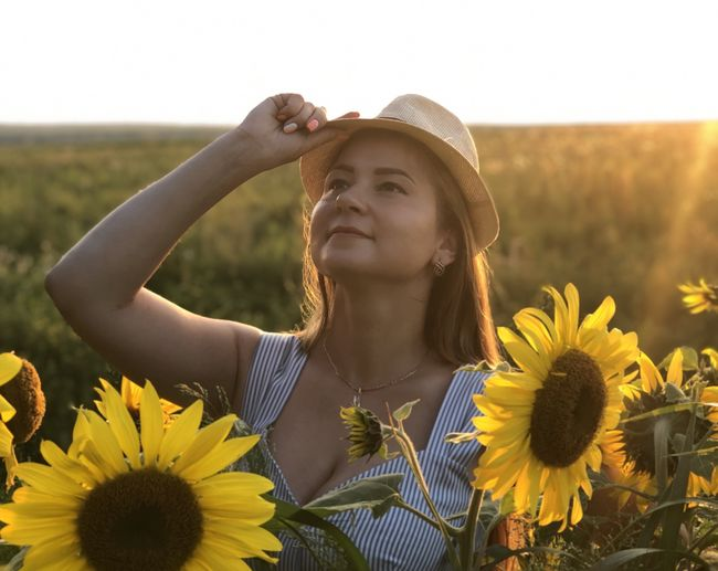 Portrait of young woman with sunflower against sky