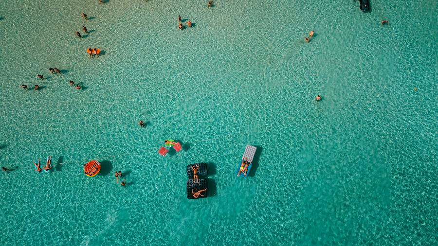 Aerial View Of People Resting In Sea During Summer