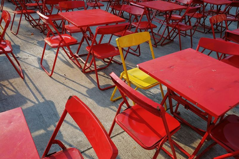 Empty chairs and tables arranging at sidewalk cafe