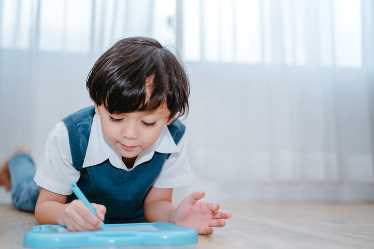 Boy Writing In Whiteboard At Home