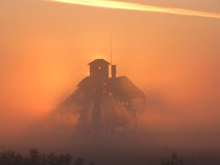 Silhouette built structure against orange sky