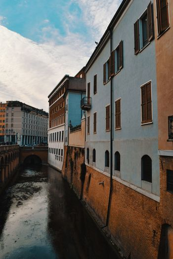 Bridge over canal amidst buildings against sky in city
