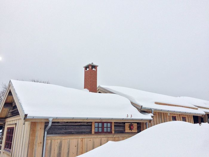 Snow on roof of building against sky