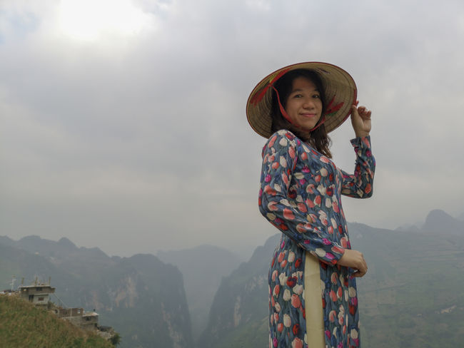 Young Vietnamese women facing and pose for camera with stunning view of the Nho Que river surrounded by mountains from the Ma Pi Leng pass in northern Vietnam Mountain Cloudy Green Color Meo Vac Vietnam Vietnamese Ao Dai Landscape People Pose Sunrise Traditional Dress Valley Women
