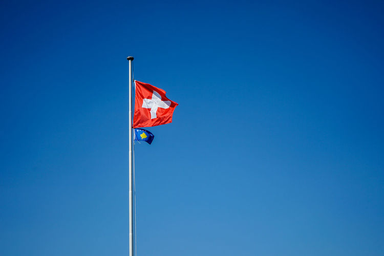 Low angle view of flags waving against clear blue sky