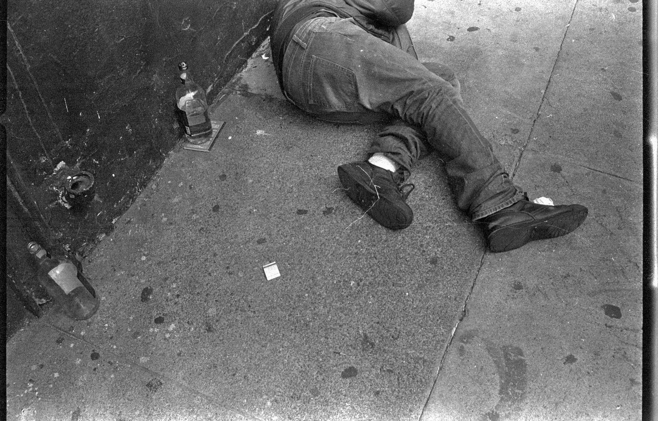 Low section of homeless man sleeping with empty liquor bottles on footpath