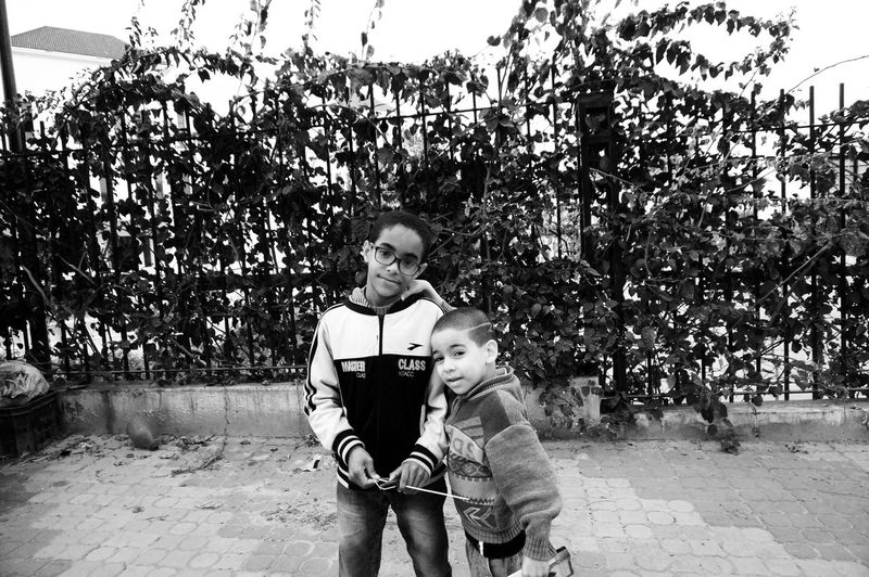 """Hey! HEEEEEEEY!! take our picture 📷"" that little guy didn't even say please 😂😂😂 Wonderful This Is My Brother Blackandwhite Hommies Little Boys Front View Street Portrait Streetphotography Holding In The Open Spontaneity Innocence Portraying Innocence Shades Of Grey Mobilephotography Shootermag AMPt_community Vscocam VSCO Snapshots Of Life Snapseed AndroidPhotography Casual Visual Witness Par Hasard"