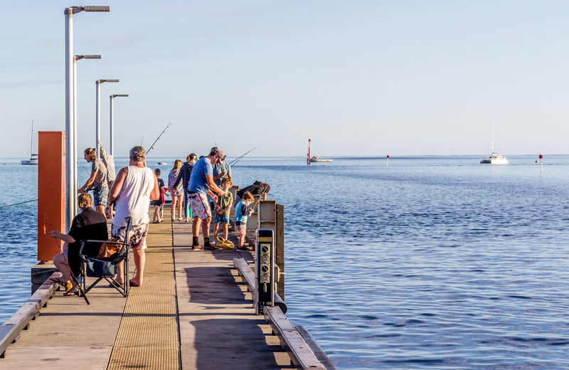 Rear view of people sitting on pier over sea against sky