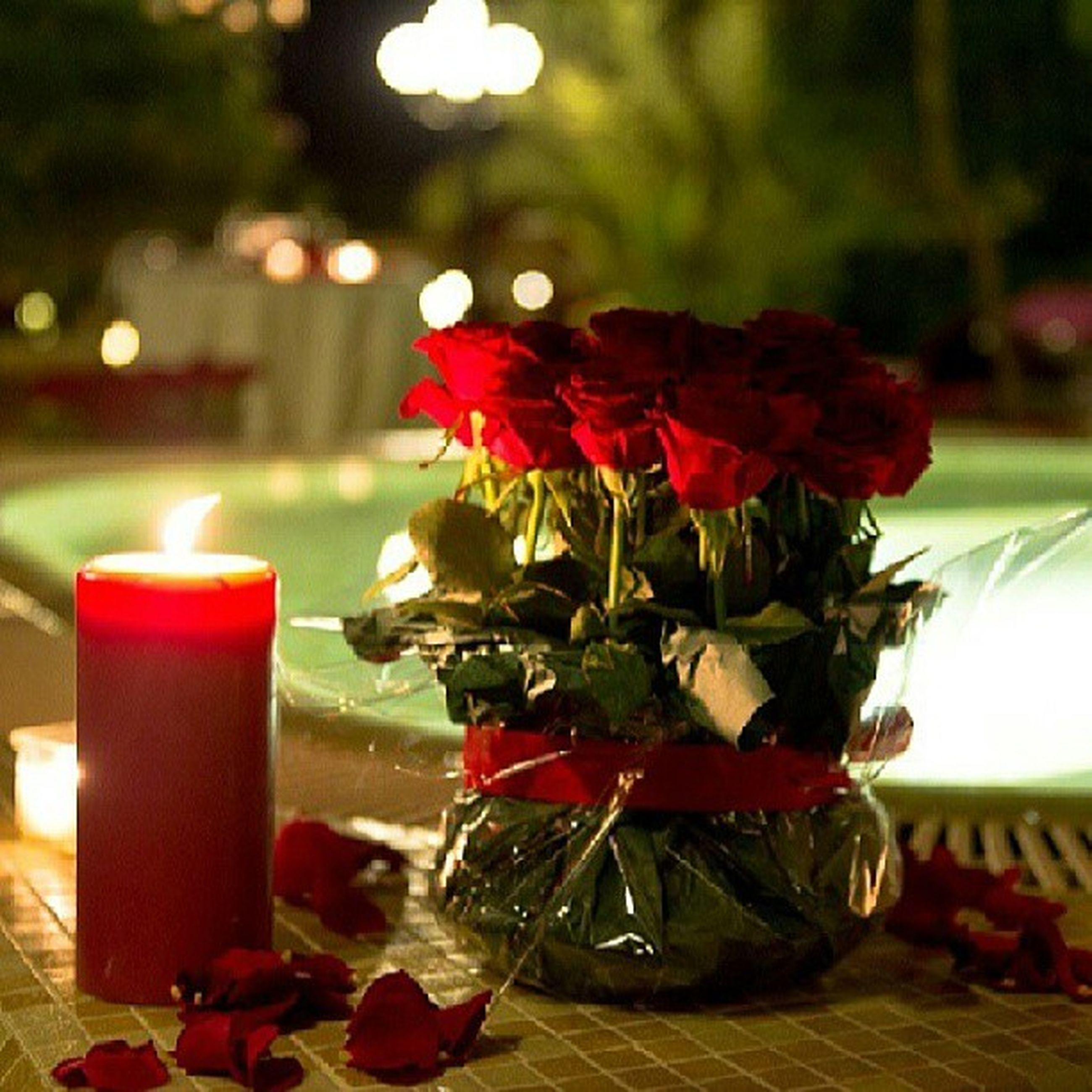 flower, red, indoors, table, vase, focus on foreground, decoration, freshness, potted plant, plant, illuminated, close-up, candle, growth, home interior, fragility, glass - material, flower pot, petal, restaurant