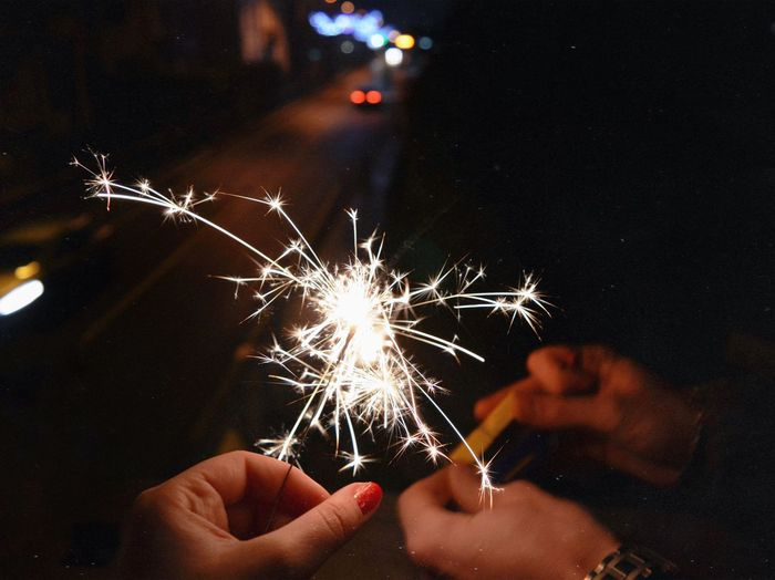 Cropped hands holding lit sparkler at night