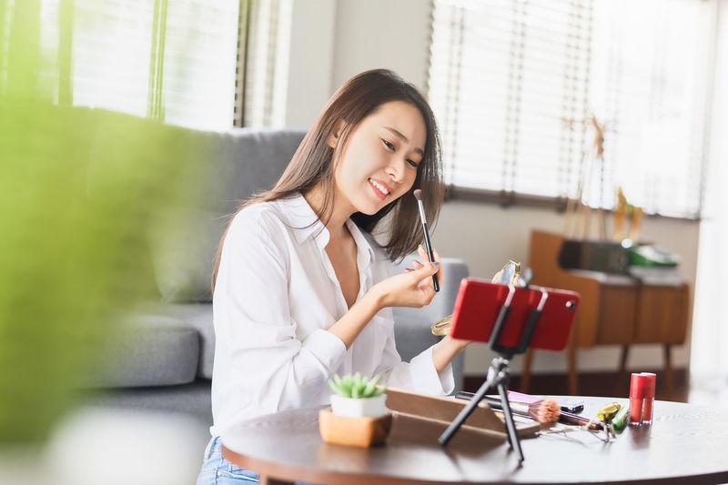 Smiling woman vlogging while applying make-up at home