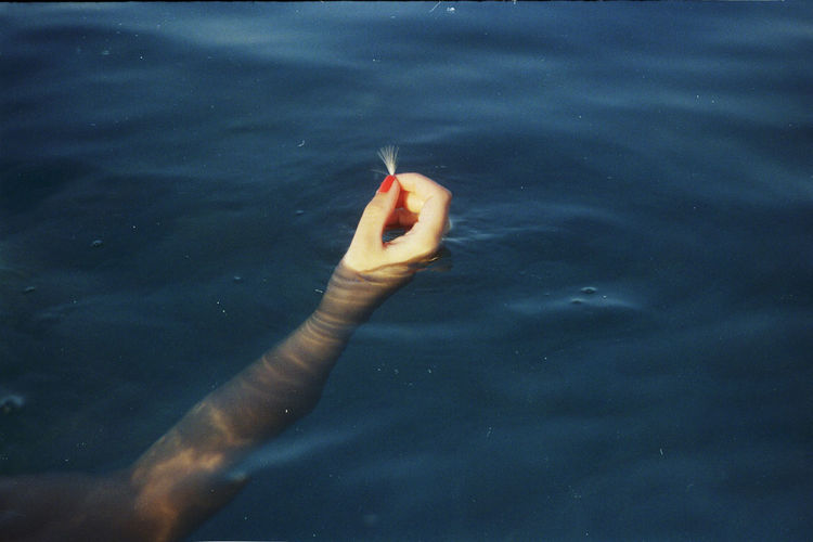Close-up of woman hand in lake