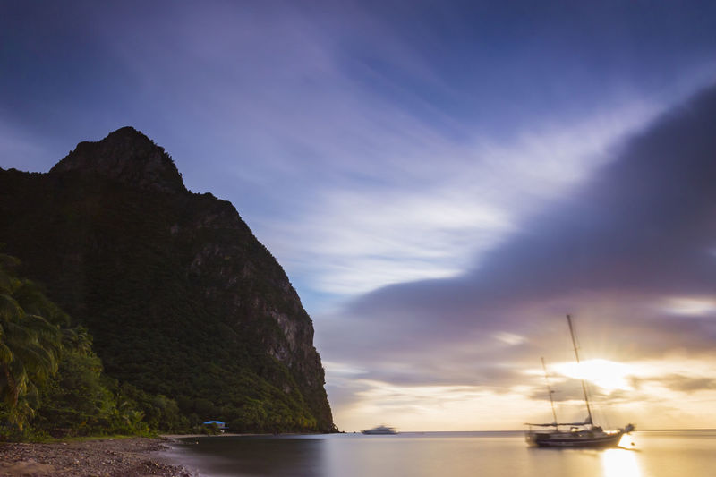 Petit Piton Sunset on Malgretoute Beach, Saint Lucia Beauty In Nature Cloud - Sky Day Mode Of Transport Moored Mountain Nature Nautical Vessel No People Outdoors Scenics Sea Sky Sunset Tranquil Scene Tranquility Transportation Water