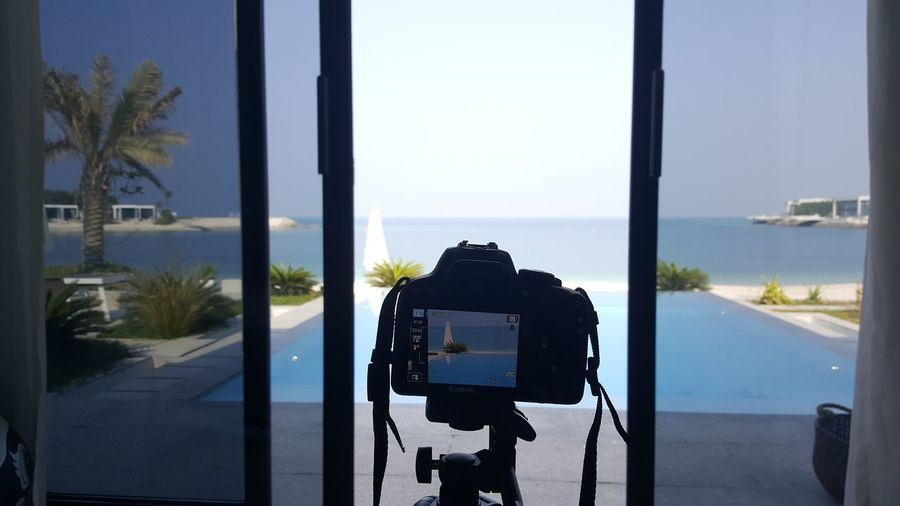 Close-up of camera by window photographing sea