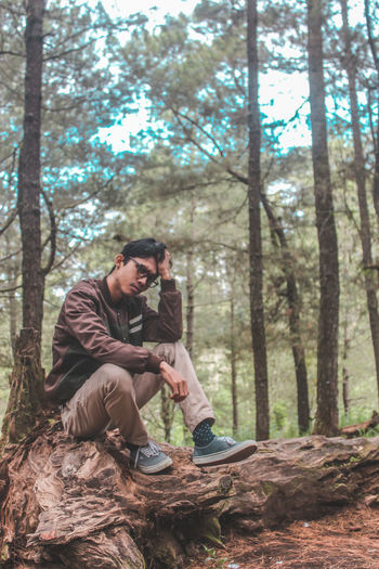 No Caption Baliphotography Portrait EyeEmNewHere EyeEm Best Edits Tree Warm Clothing Full Length Men Forest Sitting Smiling Tree Trunk Beauty Photographer Camera - Photographic Equipment Camera Photographic Equipment Photographing Paparazzi Photographer SLR Camera Beret Digital Single-lens Reflex Camera
