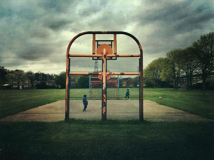 Siblings playing at basketball court