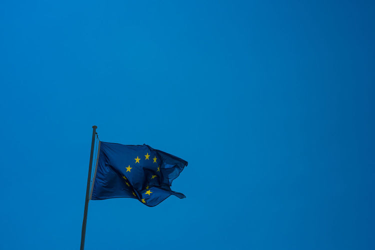 Low angle view of european community flag against clear blue sky